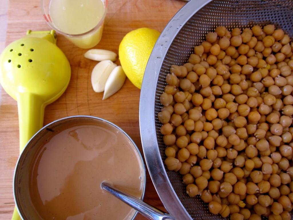 Rinse chickpeas, juice lemons, peel garlic.
