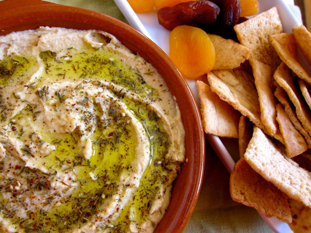 Serve, garnished with za'atar and olive oil, alongside pita or fresh veggies.